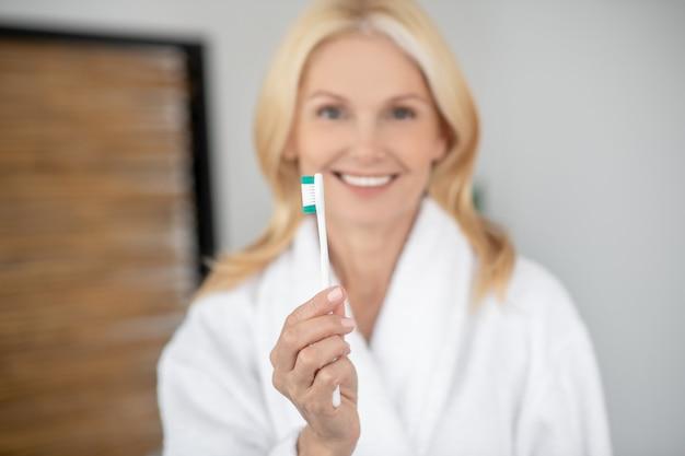 Уход за зубами. улыбающаяся блондинка чистит зубы и выглядит счастливой
