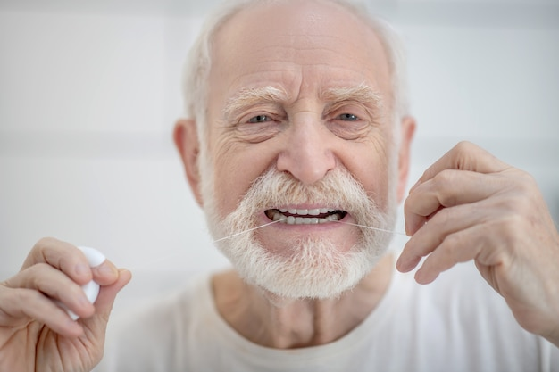 歯のクリーニング。デンタルフロスで歯を掃除する白いtシャツの白髪の男