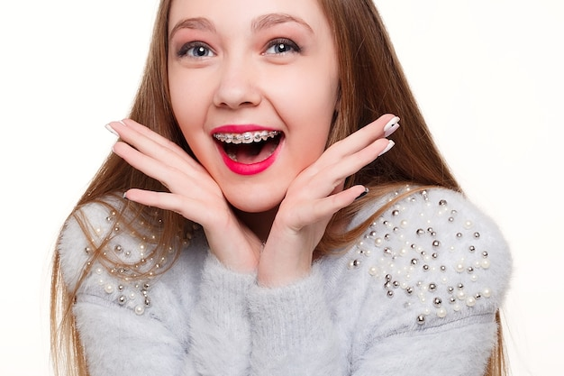 歯、感情、健康、人々、歯科医、ライフスタイルのコンセプト-健康で美しい笑顔、歯科医への子供。歯科矯正器具を持った少女の肖像。