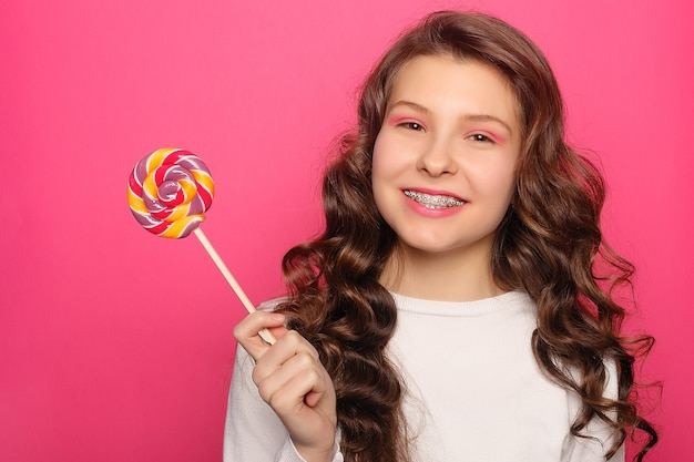 Teeth, emotions, health, people, dentist and lifestyle concept - woman with dental braces holding lollipop. healthy smile woman with clear brackets