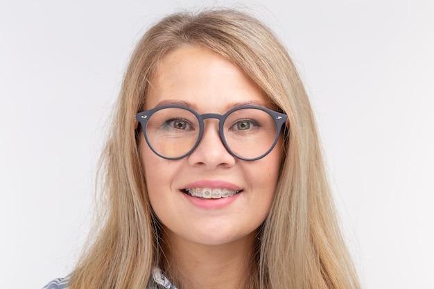 歯の健康、歯科、咬傷の矯正-白い壁に中かっこが付いた眼鏡をかけた幸せな笑顔の女性