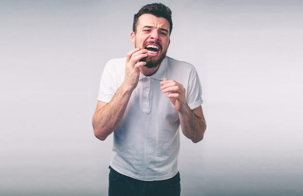 Проблема с зубами. человек, чувствующий зубную боль. макрофотография бородатый мальчик страдает от сильной зубной боли. привлекательный мужчина, чувствующий болезненную зубную боль. концепция здоровья и ухода за зубами