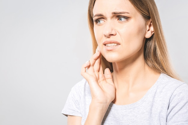 歯の問題。歯の痛みを感じる女性。強い歯の痛みに苦しんでいる美しい悲しい少女のクローズアップ。痛みを伴う歯痛を感じる魅力的な女性。歯科医療とケアの概念。高解像度
