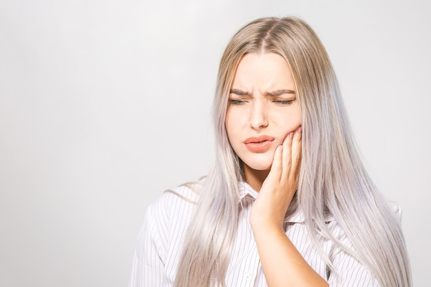 歯の問題。歯の痛みを感じる女性。強い歯の痛みに苦しんでいる美しい悲しい少女のクローズアップ