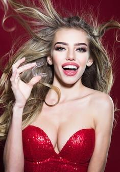 赤いドレスを着たゴージャスな女の子の手に噛み付きを改善するための歯のリテーナー。歯のケア。モバイル歯科矯正装置。女性のクローズアップは、赤い背景で隔離の手に透明な歯のアライナーを保持しています。