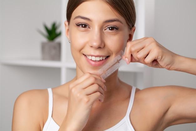 Teeth whitening, beautiful smiling woman holding a whitening strip.