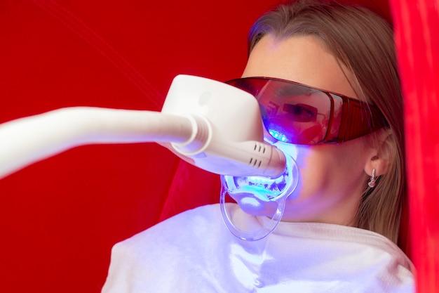 歯のホワイトニングの女の子が歯のホワイトニングのための歯にアパッチと一緒に座っています。