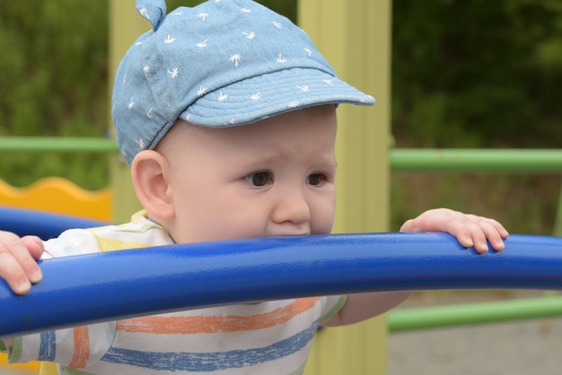 Teething baby boy on the playground
