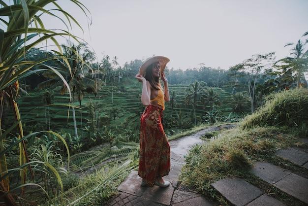 Красивая девушка посещая рисовые поля бали в tegalalang, ubud. понятие о людях, путешествиях и путешествиях