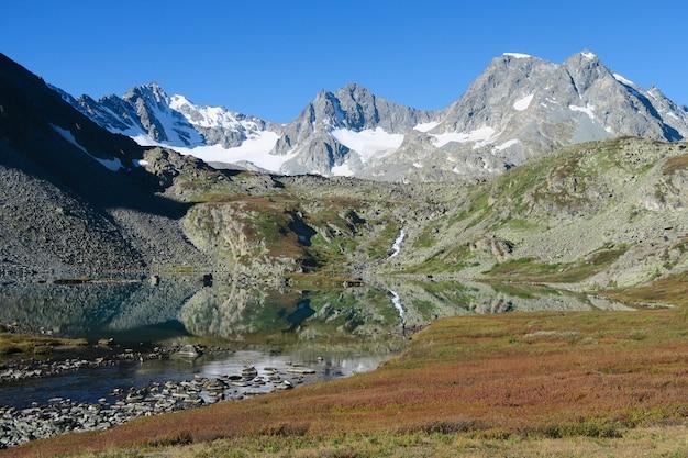 秋のクリスタルクリアマウンテンtegeek湖の風光明媚なビュー。ロシアのアルタイ山脈に落ちる
