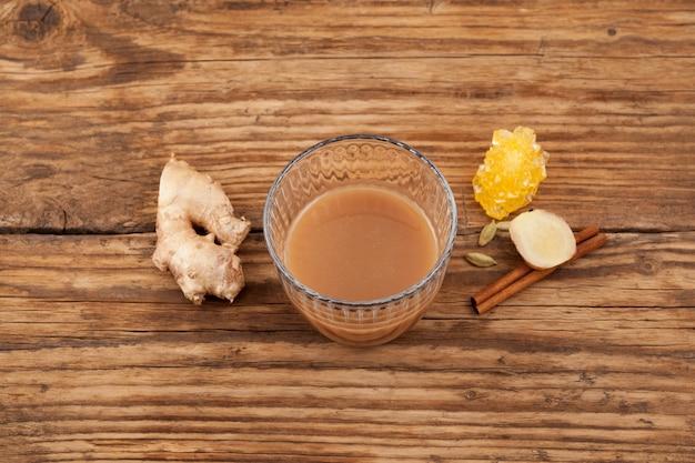 Тарик, имбирный чай в стекле на коричневом деревянном столе. популярный напиток в брунее, малайзии и сингапуре.