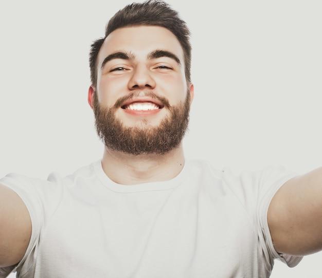 Концепция технологии: счастливое селфи. красивый молодой человек держит камеру и делает селфи и улыбается.