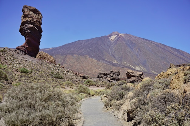 Вулкан тейде с скалой на переднем плане в солнечный день на острове тенерифе, канарские острова, испания