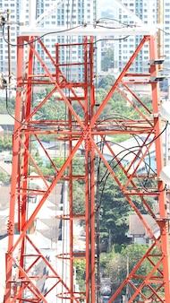 Телекоммуникационная башня крупным планом с белым и красным цветом и голубым небом.