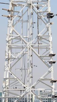 Телекоммуникационная башня крупным планом с белым цветом и голубым небом.