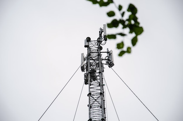 높은 타워에서 일하는 통신 엔지니어, 높은 작업의 위험 작업, 타워에서 안전 장비를 사용하는 기술자, 하늘 배경. 기술자는 타워에서 작업하는 동안 사진을 찍습니다.