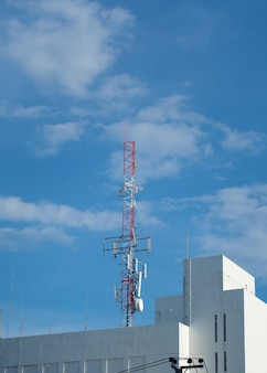 Telecommunication tower against the blue sky with clouds