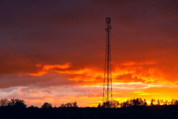 Телекоммуникационная башня против красивого закатного неба, сотовая антенна, передатчик. телеком тв радио сотовая мобильная вышка.
