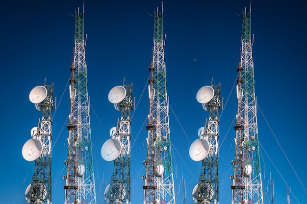 Telecommunication tower antenna on blue sky background