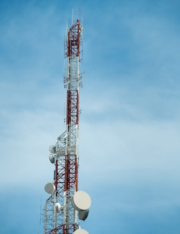 Telecommunication tower of cellular communication against the blue sky.