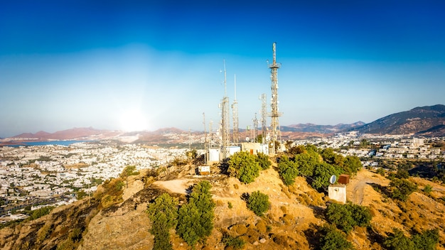Telecommunication tower on mountin with 4g 5g cellular network antenna on city background