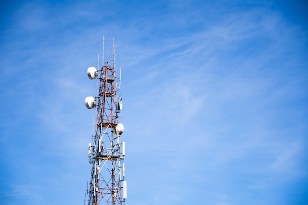 Телекоммуникационная башня беспроводных технологий против голубого неба и облаков.