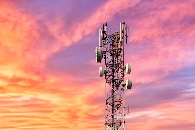 분홍색 구름 배경으로 일몰이나 새벽에 아름다운 화려한 하늘을 배경으로 안테나가 있는 통신탑.