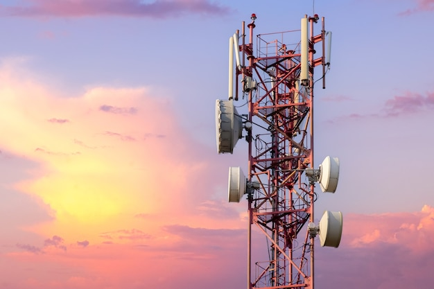 Telecommunication tower with antennas against beautiful colorful sky at sunset