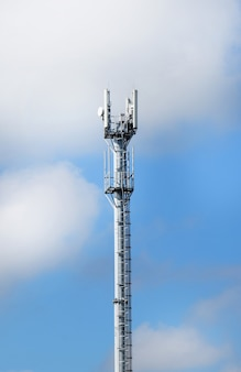 Telecommunication tower with antennas on a background of blue sky and clouds. smart antennas transmit 4g and 5g cellular signals to consumers.