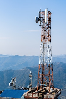 Telecommunication tower with antennas. wireless communication antenna transmitter with mountains on background. stock photo.