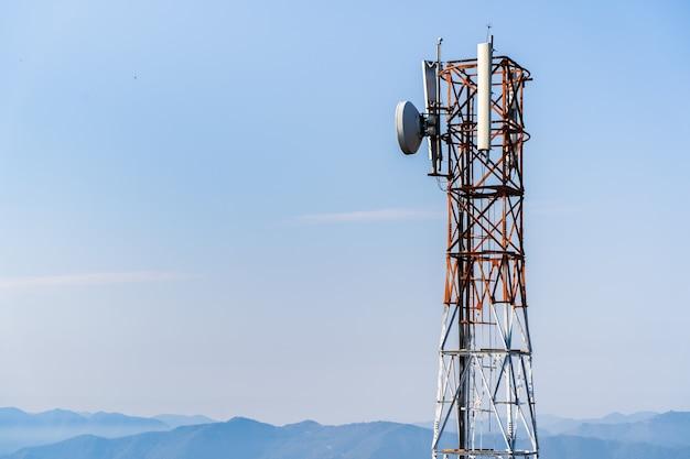 アンテナ付きの通信塔。背景に山がある無線通信アンテナ送信機。ストックフォト。