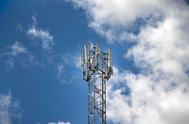Telecommunications tower with 4g, 5g transmitters. cellular base station with transmitting antennas on a telecommunications tower against the blue sky.