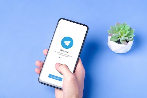스마트 폰 화면에 전보 응용 프로그램 아이콘입니다. 온라인 보안 소셜 미디어 네트워크. 파란색 배경