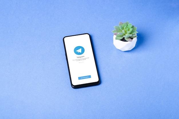 Значок приложения telegram на экране смартфона. безопасная онлайн-сеть социальных сетей. синяя поверхность