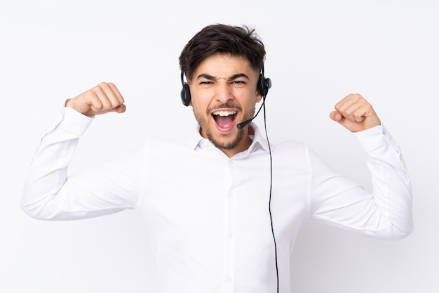 勝利を祝う白で隔離のヘッドセットで働くテレマーケティングのアラビア人男性