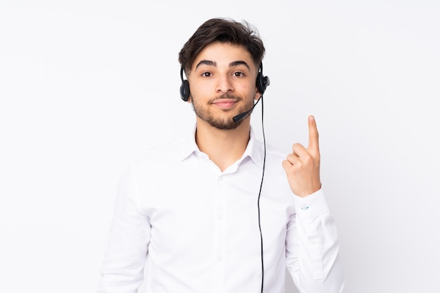 흰 벽에 헤드셋을 사용하는 텔레마케터 아라비아 사람은 검지 손가락으로 가리키는 좋은 아이디어