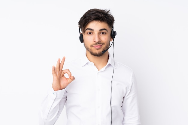Telemarketer arabian man working with a headset isolated on white wall showing an ok sign with fingers
