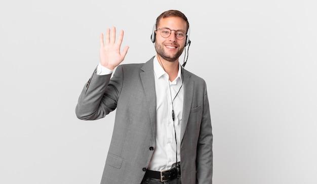 텔레마케터 사업가는 행복하게 웃고 손을 흔들며 환영하고 인사합니다.