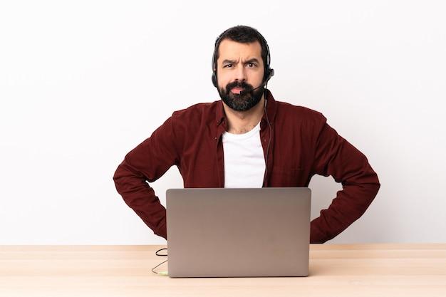Кавказский человек телемаркетинга работает с гарнитурой и с ноутбуком сердится.