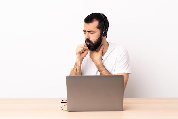 Кавказский человек телемаркетинга, работающий с гарнитурой и с ноутбуком, много кашляет.