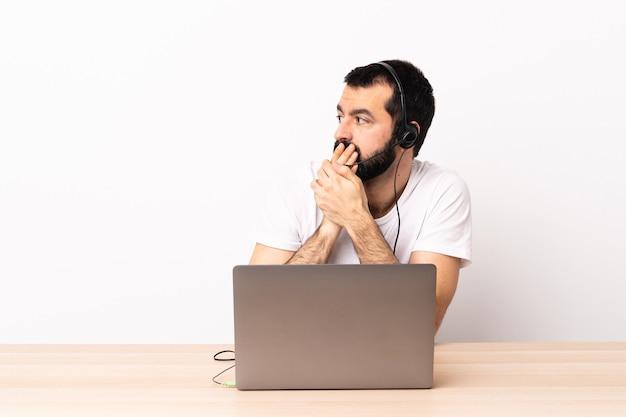 텔레마케터 백인 남자는 헤드셋으로 작업하고 노트북으로 입을 덮고 측면을 찾고 있습니다.