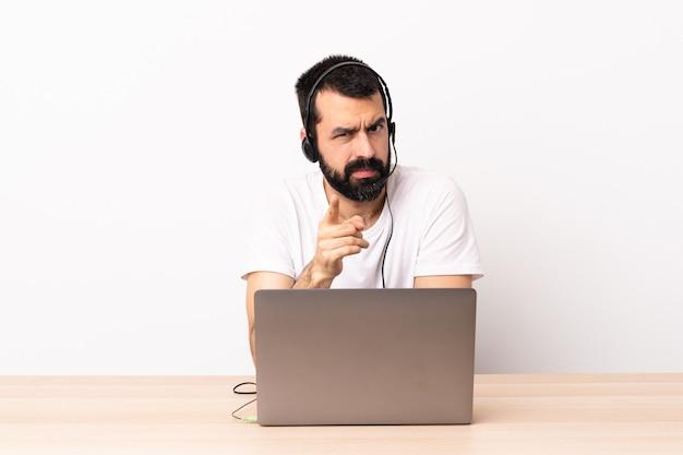 テレマーケティングの白人男性のヘッドセットとラップトップを使用してイライラして前方を向く