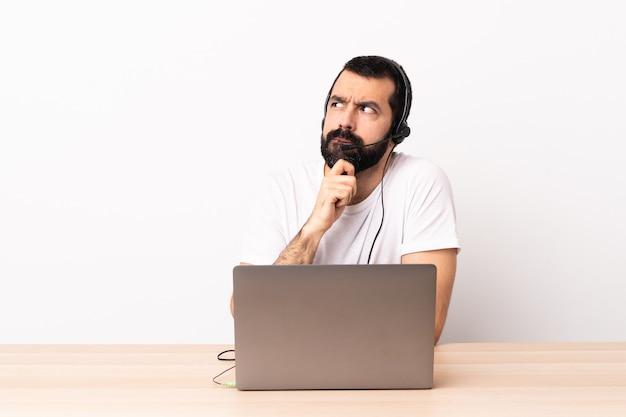 Телемаркетер кавказских человек работает с гарнитурой и с ноутбуком, имея сомнения и мышления.