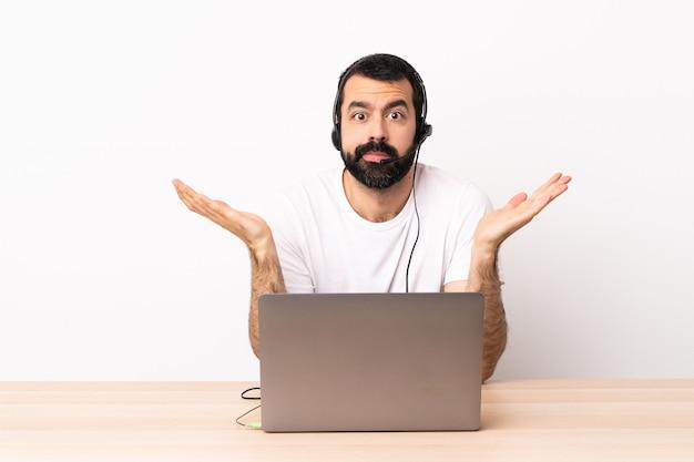 헤드셋을 사용 하 고 손을 올리는 동안 의심을 가지고 노트북으로 일하는 텔레마케터 백인 남자.