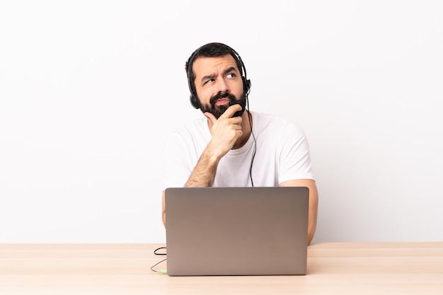 Телемаркетер кавказский человек работает с гарнитурой и с ноутбуком, имея сомнения
