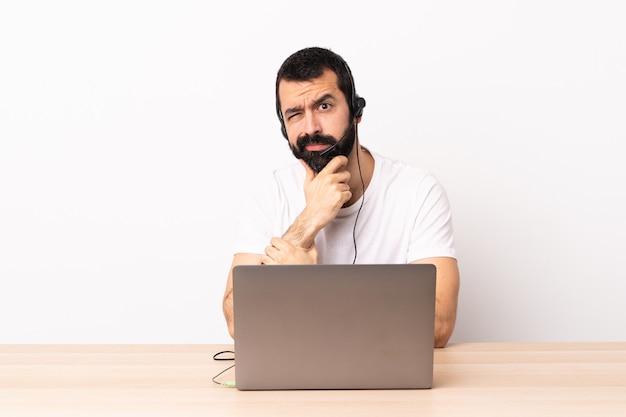 Телемаркетер кавказский человек, работающий с гарнитурой и с ноутбуком, возникают сомнения.