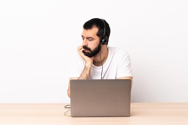 Кавказский человек телемаркетинга работает с гарнитурой и с ноутбуком, сомневаясь.