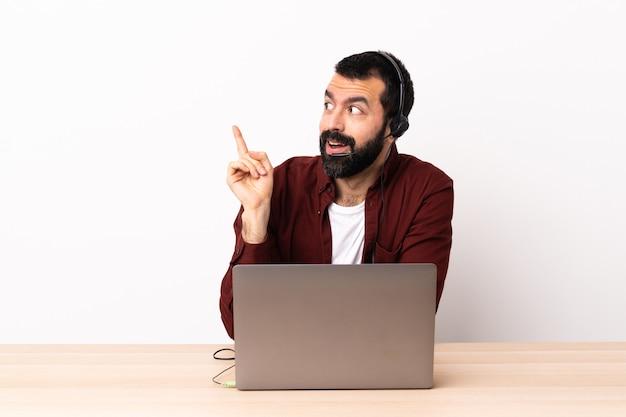헤드셋을 사용하고 노트북을 사용하는 텔레마케터 백인 남자는 손가락을 들어 올리면서 솔루션을 실현하려고합니다.