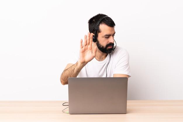 ヘッドセットとラップトップで作業しているテレマーケティングの白人男性が停止ジェスチャーをしてがっかりしました。