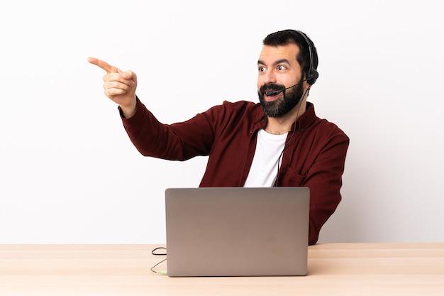 Кавказский человек телемаркетинга работает с гарнитурой и с ноутбуком, указывая прочь.